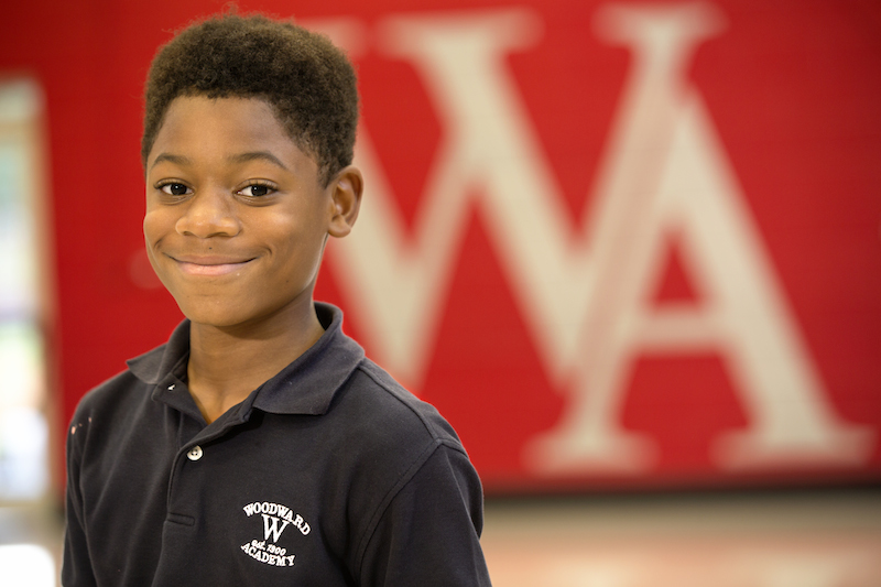Woodward Academy student standing in front of WA background