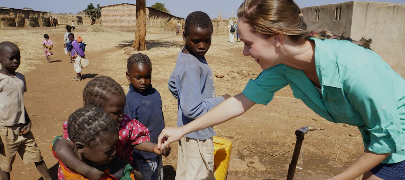 student holding hands with child in Zambia